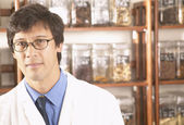 Asian male herbalist doctor in front of Chinese medicinal herbs — Stock Photo