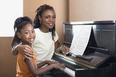 Figlia di aiutare madre africana con lezioni di pianoforte — Foto Stock