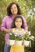 Hispanic mother and daughter with potted flowers outdoors — Stock Photo