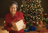 Senior Hispanic woman holding gift in front of Christmas tree — Stock Photo
