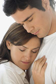 Studio shot of couple hugging with eyes closed — Stock Photo