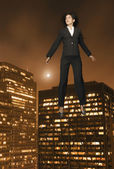 Businesswoman floating above the city — Stock Photo