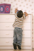 Young boy reaching on dresser — Stock Photo