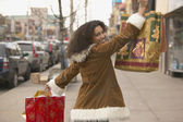 Young woman holding up shopping bags — Stok fotoğraf