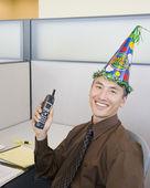 Asian businessman wearing birthday hat — Stock Photo