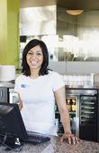 Portret van tienermeisje caissière in restaurant — Stockfoto