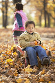 African girl pulling brother in wagon — Stock Photo