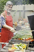 Middle-aged man grilling vegetables — Stock Photo
