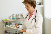 Female doctor writing on clipboard — Stock Photo