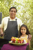 Hispanic father and daughter next to barbecue grill with kebabs — Stock Photo