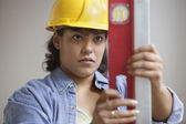 Woman construction worker in hard hat reading level measurements — Stock Photo