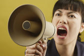 Asian businesswoman yelling into megaphone — Stock Photo
