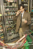Asian businessman on cell phone in grocery store — Stock Photo