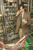 Azjatycki biznesmen na telefon komórkowy w sklepie spożywczym — Zdjęcie stockowe