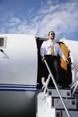 Asian male pilot exiting airplane — Stock Photo