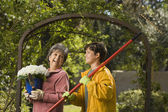 Grandmother and grandson with potted plant and rake — Stockfoto