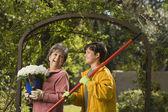Großmutter und enkel mit topfpflanze und rechen — Stockfoto