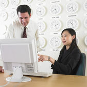 Businessman and businesswoman working with time zone clocks on the wall behind them — Stock Photo