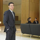 Businessman standing in lobby — Stock Photo