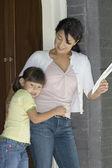 Mother and daughter standing in doorway — Stock Photo