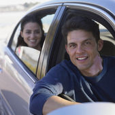 Young man driving a car with woman in backseat — Stock Photo