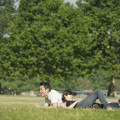 Young couple lounging in grass — Stock Photo