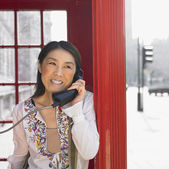 Asian woman using public telephone box in urban area in London — Stock Photo