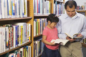 Father and daughter looking at library books — Foto de Stock