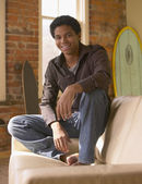 Young African man sitting on arm of sofa smiling — Stock Photo