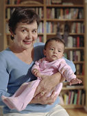 Middle-aged woman cradling her baby granddaughter — Stock Photo