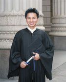 Young male graduate holding a degree — Stock Photo