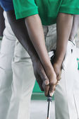 Close up of father and son's hands golfing — Stockfoto