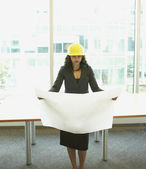 Businesswoman wearing hard had and looking at blueprints — Stock Photo