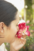 Hispanic woman smelling flower — Stock Photo