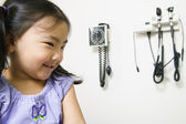 Young girl sitting in a doctor's office — Stock Photo