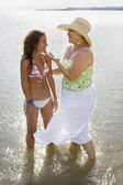 Hispanic mother and daughter wading in water — Stock Photo