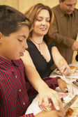 Hispanic mother helping son cut food — Stock Photo