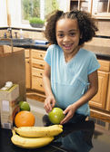African girl with groceries in kitchen — Stock Photo