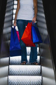 Woman on escalator with shopping bags — Стоковое фото