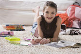 Young girl doing homework on floor — Stock Photo