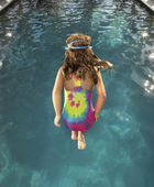Young girl in mid-air above a swimming pool — Stock Photo