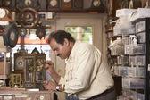Profile of man fixing clock in repair shop — Stock Photo