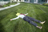 Businessman lying in the grass with a file folder over his face — Stock Photo