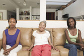 Portrait of three generations of women sitting on couch — Stock Photo