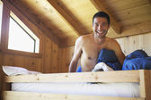 Man sitting in wooden bunk — Stock Photo