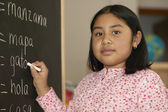 Portrait of girl writing on chalkboard — Stock Photo