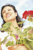 Low angle view of woman holding plant — Stock Photo