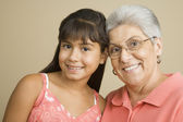 Studio shot of Hispanic grandmother and granddaughter smiling — Stock Photo