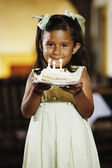 Young girl holding a piece of birthday cake — Stock Photo