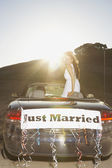 Bride standing in convertible with Just Married banner on the back — Stock Photo